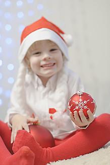 Boy holding christmas bauble, smiling, portrait - MJF000151