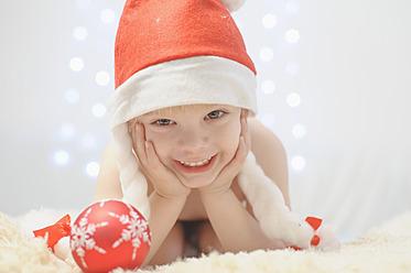 Boy holding christmas bauble, smiling, portrait - MJF000146