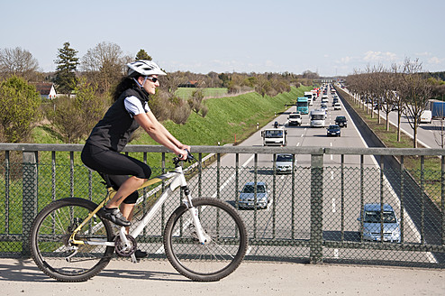Germany, Mid adult woman with mountain bike on bridge looking at traffic on highway - UMF000511