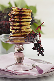 Stacked pancakes on cakestand with elderberry on plate - ECF000103