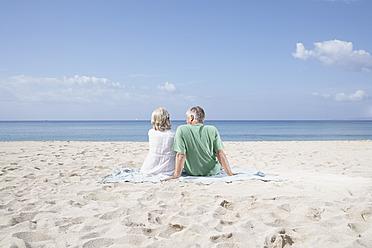Spain, Mallorca, Senior couple sitting at beach - PDYF000204