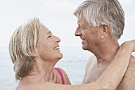 Spain, Senior couple looking at each other, smiling - PDYF000257
