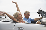 Spain, Senior couple in convertible car, smiling - PDYF000230