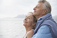 Spain, Senior couple on beach at Atlantic, smiling - PDYF000221