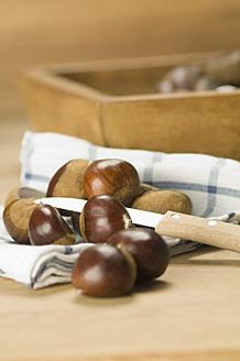 Close up of chestnuts on cloth with knife - ASF004658