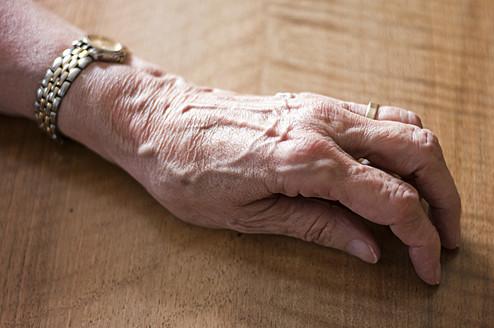 Germany, Hesse, Frankfurt, Human hand on table - MUF001250