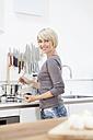 Germany, Bavaria, Munich, Woman preparing food in kitchen - RBYF000326