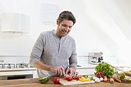 Germany, Bavaria, Munich, Man chopping vegetables in kitchen - RBYF000255