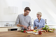 Germany, Bavaria, Munich, Mature couple chopping vegetables in kitchen, smiling - RBYF000257