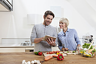Germany, Bavaria, Munich, Mature couple preparing food while looking digital tablet - RBYF000258