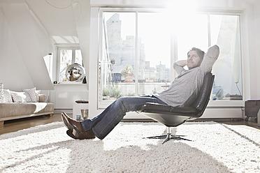 Germany, Bavaria, Munich, Man sitting on armchair - RBYF000284