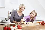Germany, Bavaria, Munich, Mother and daughter preparing pizza in kitchen - RBYF000296