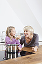 Germany, Bavaria, Munich, Daughter feeding mother in kitchen, smiling - RBYF000305