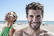 Spain, Mid adult couple sitting at beach, smiling - WESTF018961