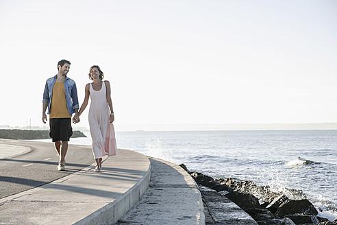 Spain, Mid adult couple walking along coast - WESTF019015