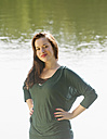Germany, Berlin, Young woman standing at lake, smiling, portrait - BFRF000127