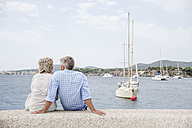 Spain, Senior couple sitting at harbour - WESTF019047
