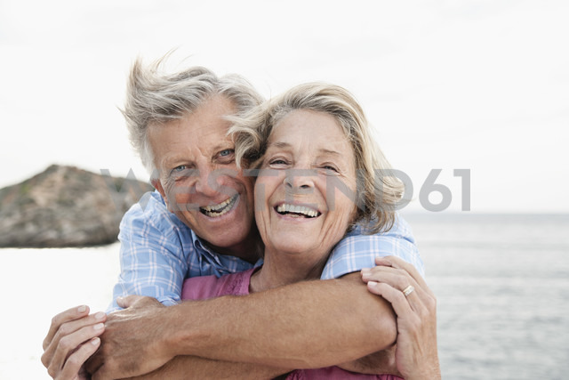 Spain, Senior couple embracing at harbour, smiling - WESTF019050