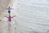 Spain, Seniors couple walking along beach - WESTF019071