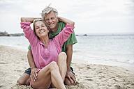 Spain, Seniors couple sitting on beach - WESTF019080