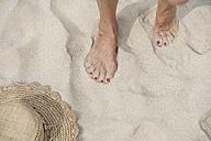 Spain, Senior woman walking on beach - WESTF019086