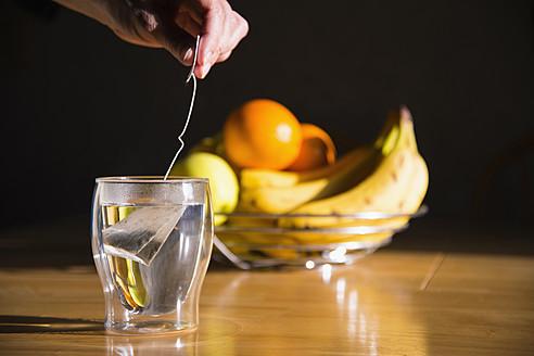 Human hand preparing tea, bowl of fruits in background - ABAF000371