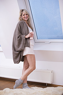 Young woman standing at window with coffee, smiling, portrait - VRF000094