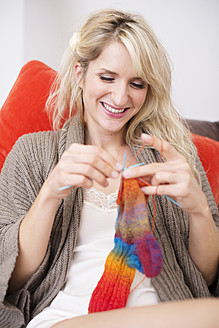 Young woman sitting on couch and knitting - VRF000102