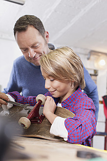 Germany, Leipzig, Father and son repairing skateboard - BMF000578