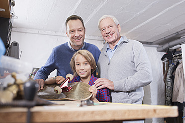 Germany, Leipzig, Grandfather, father and son repairing skateboard - BMF000581