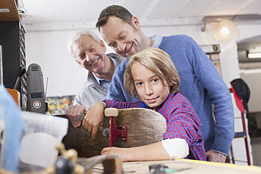 Germany, Leipzig, Grandfather, father and son repairing skateboard - BMF000584
