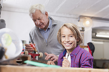 Germany, Leipzig, Grandfather and son repairing skateboard - BMF000590