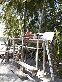 Central America, Costa Rica, Man sitting on wooden high seat under palms - BSCF000205