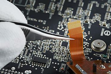 Human hand repairing printed circuit board, close up - DSCF000009