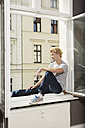 Germany, Berlin, Young man sitting at open window - SKF000949