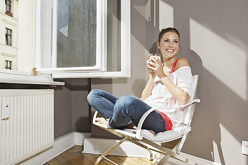 Germany, Berlin, Young woman sitting at open window, smiling - SKF000961