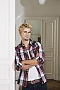 Germany, Berlin, Young man standing beside door, smiling - SKF000982