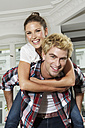Germany, Berlin, Young man giving piggy back ride to woman - SKF000988