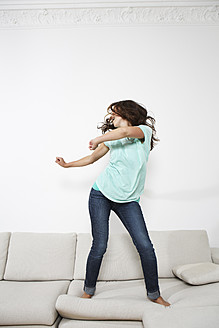 Germany, Berlin, Young woman dancing on couch - SKF001024