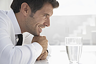 Spain, Businessman thinking, smiling - PDYF000333