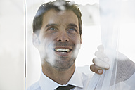 Spain, Businessman thinking, smiling - PDYF000345