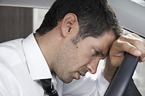 Spain, Dispressed businessman driving car - PDYF000360