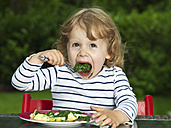 Germany, Duesseldorf, Girl sitting outside and eating spinach, smiling, portrait - STKF000045