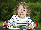Germany, Duesseldorf, Girl sitting outside and eating spinach, smiling, portrait - STKF000046