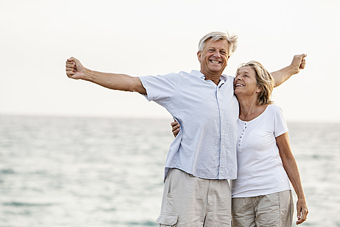 Spain, Senior couple having fun at the sea - JKF000012