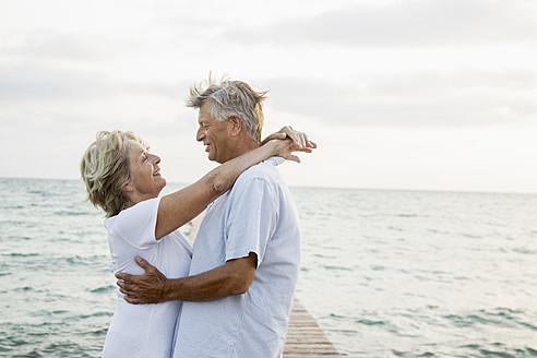 Spain, Senior couple embracing at the sea - JKF000015