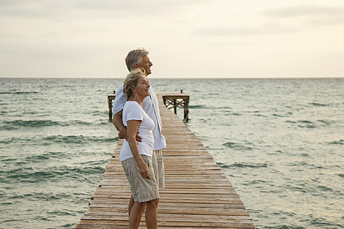 Spain, Senior couple standing on jetty at the sea - JKF000024