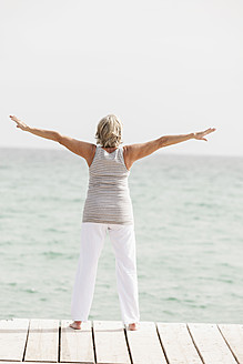 Spain, Senior woman exercising on jetty at the sea - JKF000039