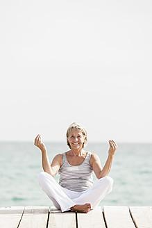 Spain, Senior woman doing yoga on jetty at the sea - JKF000042