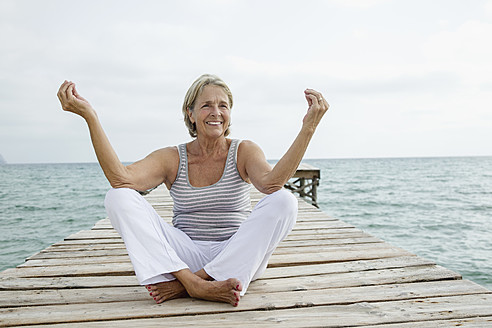 Spain, Senior woman doing yoga on jetty at the sea - JKF000045